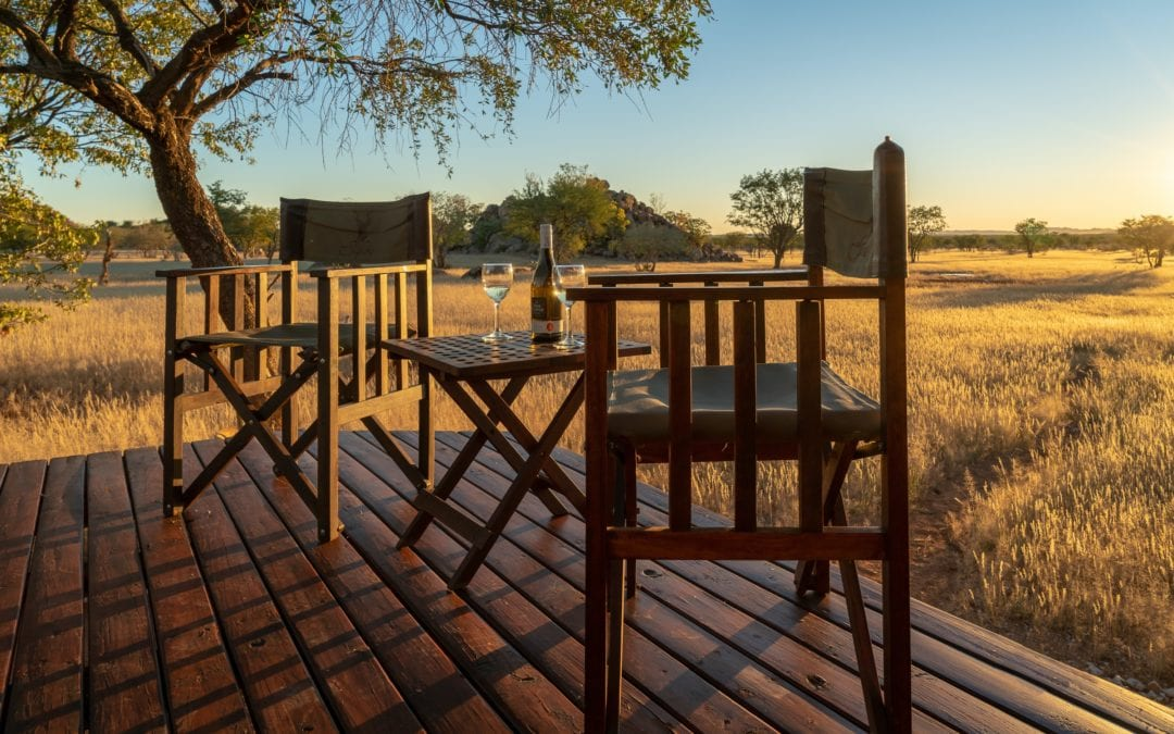 Romantic setting with chairs, a bottle of wine and the beautiful Ohorongo Game Reserve in the background during sunset.